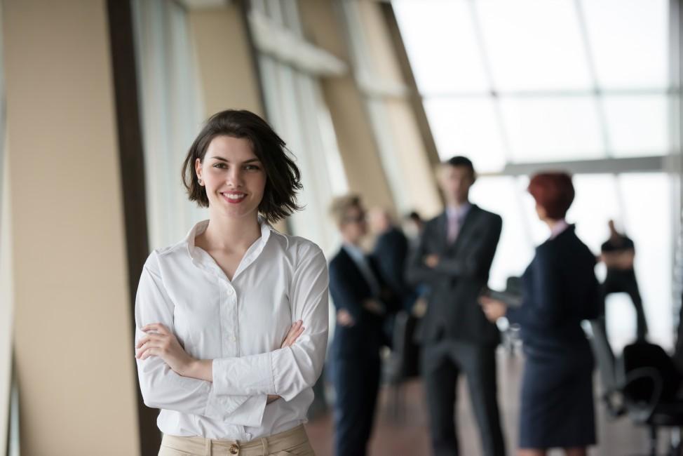 zdjęcie przedstawia kobietę jaka stoi przedem i jaka się uśmiecha, a za nią inne osoby