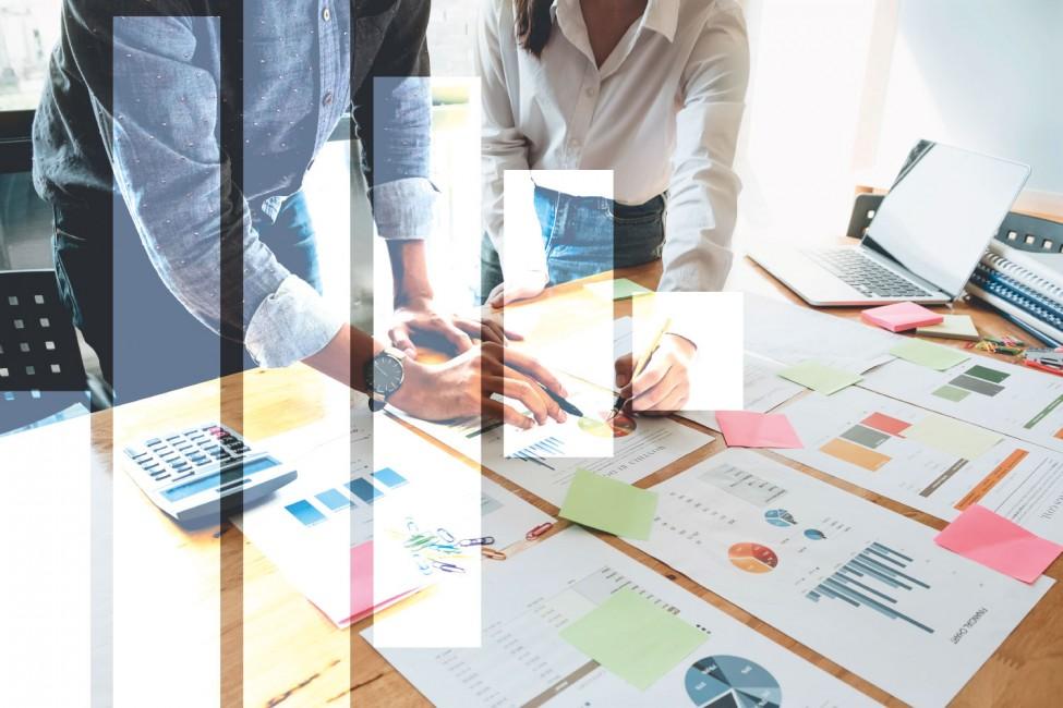 zdjęcie przedstawia ręce osób pracujących z dokumentami na stole