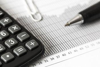 zdjęcie przedstawia kalkulator, ołówek oraz wykres