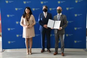 zdjęcie przedstawia trzy osoby stojące i przekazujące sobie dokument