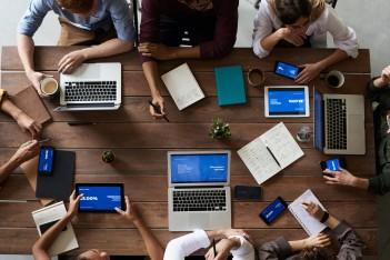 obraz przedstawia komputery stojące na stole oraz zespół pracowników pracujących na nich
