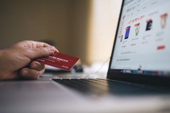 obraz przedstawia dłonie osoby robiącej zakupy za pośrednictwem laptopa