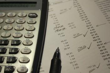 obraz przedstawia kalkulator oraz kartkę papieru, na jakiej zapisane są obliczenia