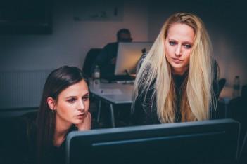 zdjęcie przedstawia dwie kobiety stojące za komputerem podczas pracy