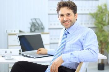 na zdjęciu widać mężczyznę siedzącego przy biurku, na jakim stoi komputer