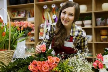 zdjęcie przedstawia kwiaciarkę pochylającą się nad kwiatami