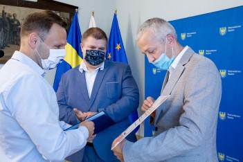 zdjęcie przedstawia trzy osoby przekazujące sobie dokumenty